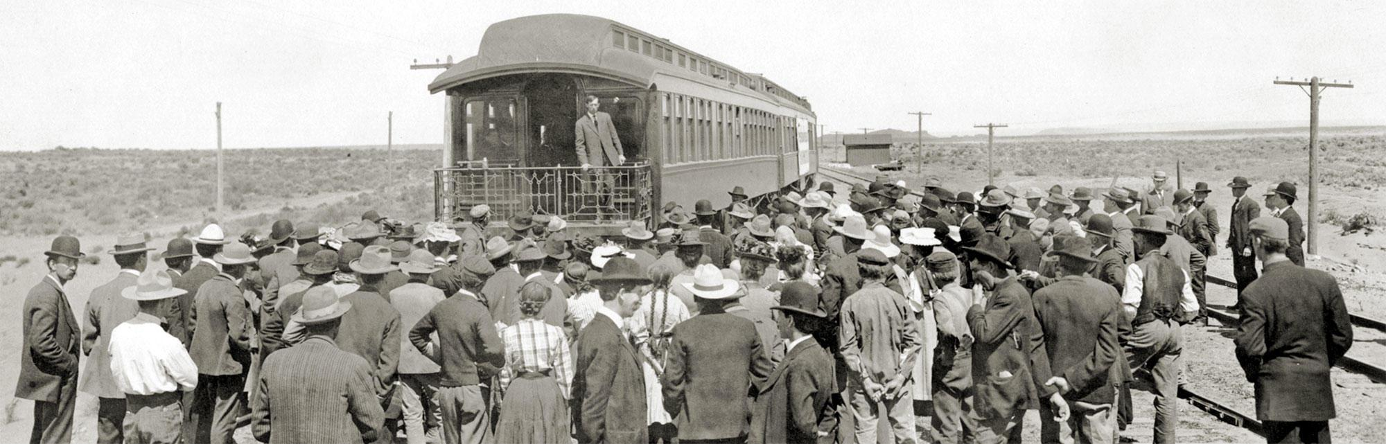 More than eighty people gather at the back of a train to listen to a farming demonstration lesson.