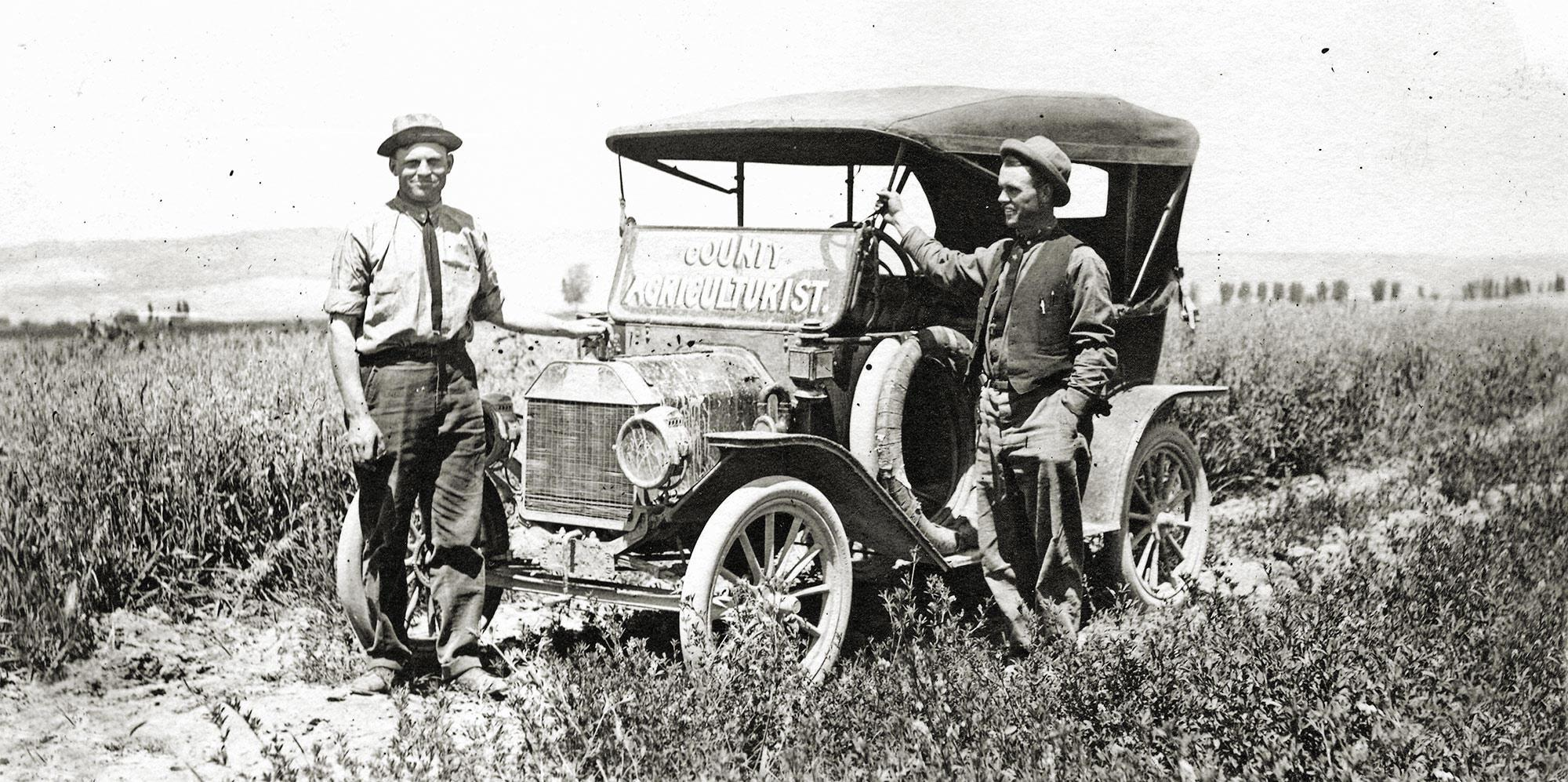 "Two OSU Extension agents stand by a car in the middle of the field. ""County Agriculturist"" is written across the car's front window."