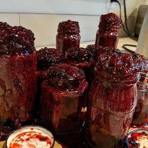 jars of jam on a kitchen counter overflowing making a sticky mess.