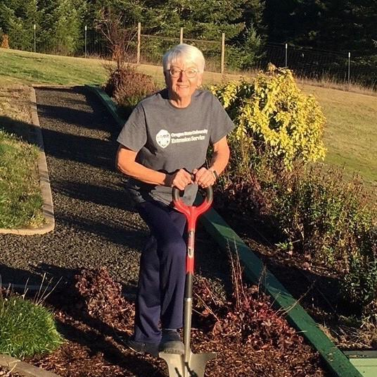 Smiling woman with shovel in a rose garden.