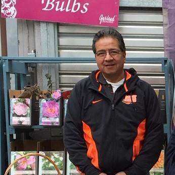 Man standing next to a display of flower bulbs