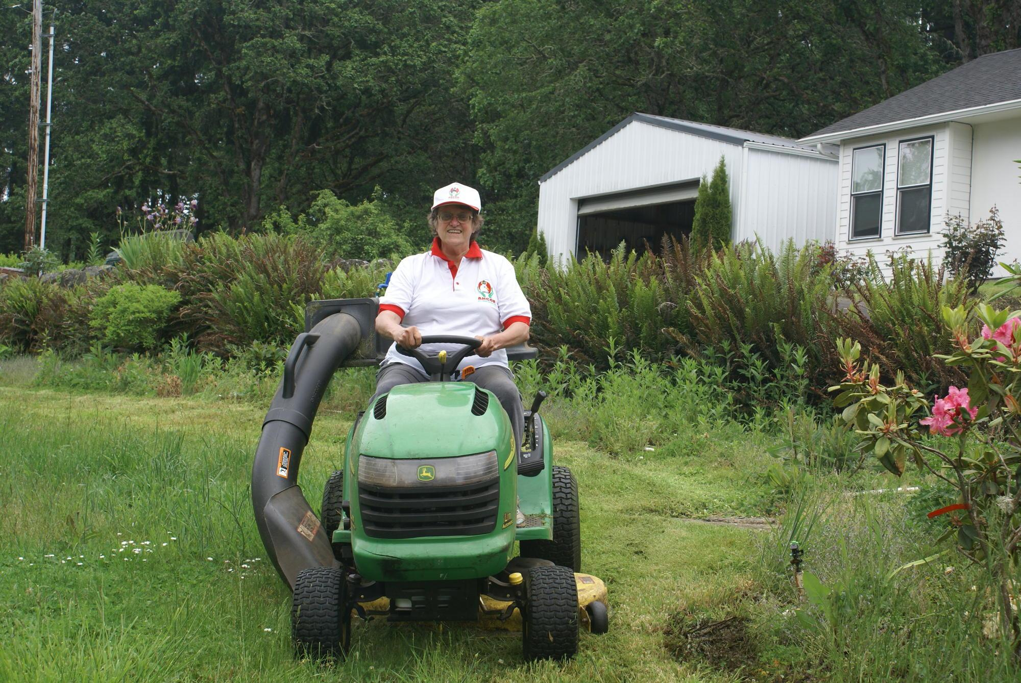 Woman wearing a ballcap riding a lawn tractor.