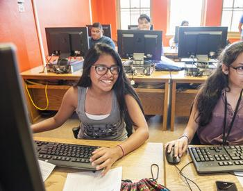 Youth smiles while at a computer