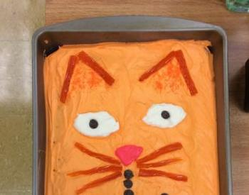 Cake decorated to look like an orange cat wearing a bowtie