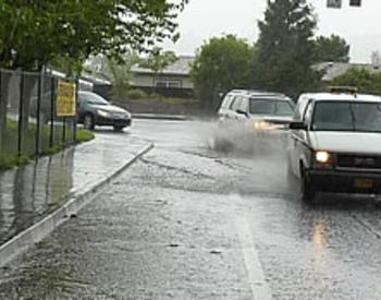 cars driving through standing water on a road