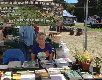 Master Gardener volunteer sits at informational table with educational pamphlets and plants. Mobile Plant Clinic banner in background