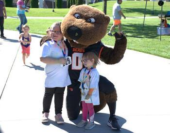 Benny, Oregon State University's mascot, poses with two children at Benny Bash.