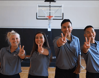 Four youth holding up two fingers on a basketball court