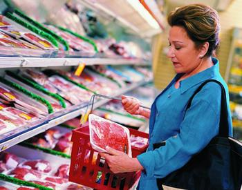 Woman selecting package of meat at store