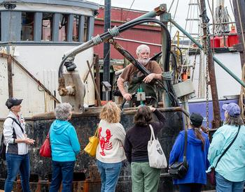 A group of people talks with a fisherman during a Shop at the Dock tour in Garibaldi.