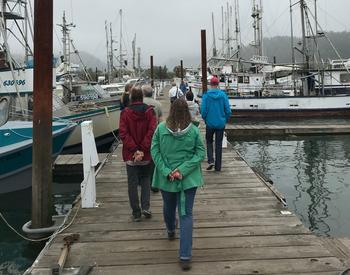 A group of tours the docks at Port of Garibaldi during a Shop at the Dock tour