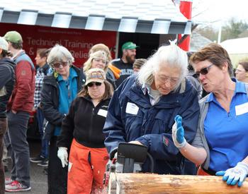 Jean Azlein (left) of McMinnville makes practice cuts under the guidance of instructor Alison Henynderickx in the Women and Chainsaw Safety course at the 2019 Clackamas Tree School.