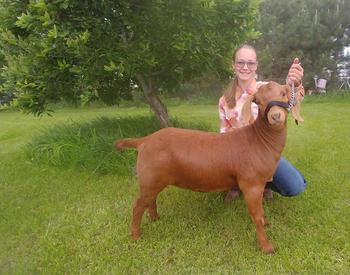 McKenzie Shelden poses with her Boer goat.