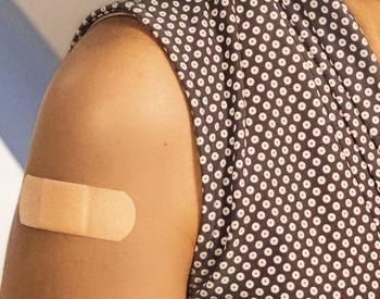 Photo of person's arm with bandage after receiving a vaccination
