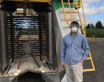 Wei Qiang Yang, associate professor and berry Extension agent for Oregon State University Extension Service, stands in front of a blueberry harvester that uses a soft catch mechanism.