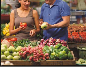 A man and woman look at produce at a farmers market.
