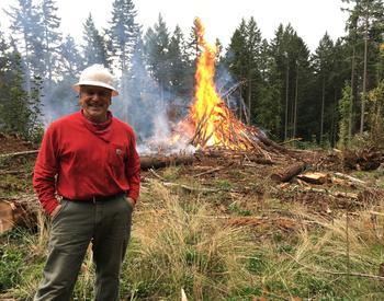 Man in hard hat with a burning pile of debris in forest setting