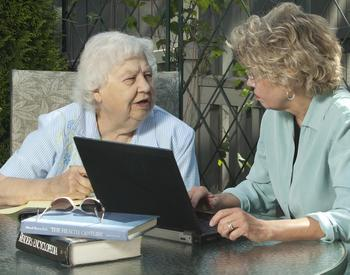 Two women, one who is a senior, discussing at a laptop