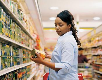 Woman looking at canned goods in store