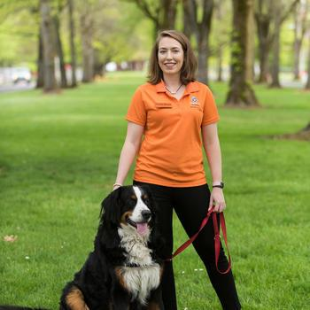 Dr. Kristen Moore standing next to her Bernese Mountain Dog, Beau.